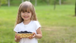 Child holding a basket of black currant. She shows the tongue