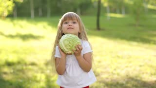 Child holding a cabbage vegetables