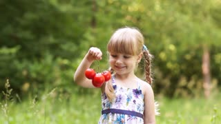 Child holding a tomato. Touching the vegetable and looks into the camera