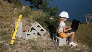 Child is the builder. Girl in the construction helmet and with sunglasses. She is holding laptop. Thumbs up. Ok. Panning