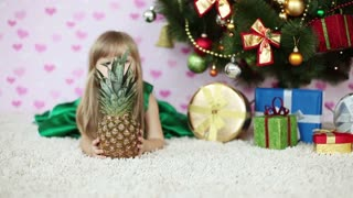 Child looks out over the pineapple lying on the floor near the Christmas Tree
