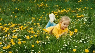 Child lying on the grass among yellow flowers. Zooming