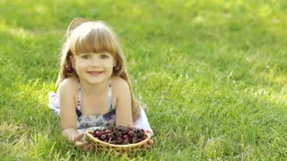 Child lying on the grass with a sweet cherry fruit