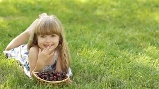 Child lying on the grass with a sweet cherry
