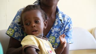 Child On Mother's Lap In Haiti
