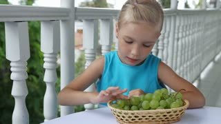 Child playing in the Kids Count and eating grapes. Child shows Ok. Thumbs up. Delicious grapes