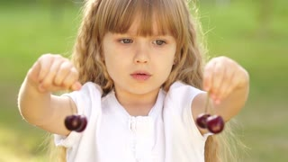 Child playing with a sweet cherry fruit