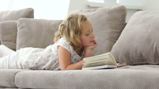 Child reading the book and lying on the sofa