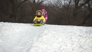 Child riding on a sled down the hills