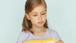 Child showing corn. Girl holding corn in the hands. Closeup