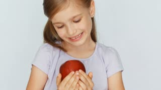 Child showing red apple. Girl holding a red apple in the palm. Closeup