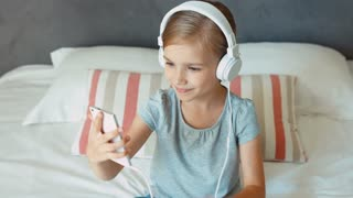 Child sitting on the bed and listening music in headphones from smartphone cell phone and dancing. Thumb up. Ok. Zooming