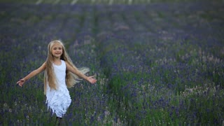 Child spinning in the field. Girl looking at the camera. Butterfly is flying. Slow motion