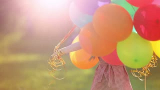 Child spinning with balloons in the park.  Girl looking at camera. Lens flare and sunlight