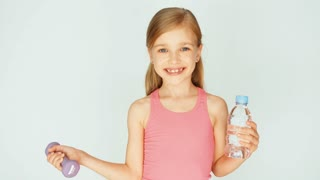 Child turns around at camera. Girl holding dumbbell and bottle of water on a white background and laughing. Zooming