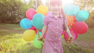 Child walking with balloons in the park. Girl looking at camera. Lens flare and sunlight