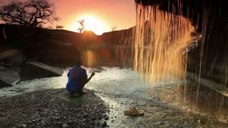 Child Watching a Waterfall and Tossing a Rock 2