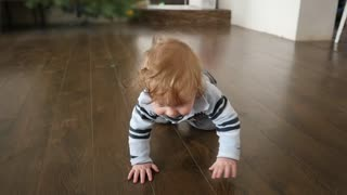 Childhood, babyhood and people concept - happy little baby crawling in living room at home
