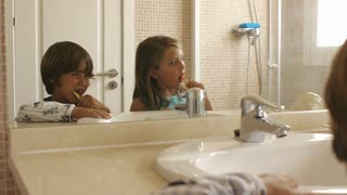 Children brushing their teeth in bathroom.