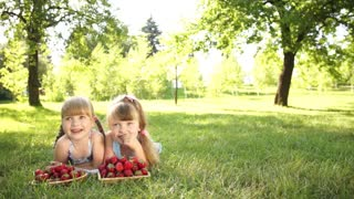 Children lying on the grass with strawberries