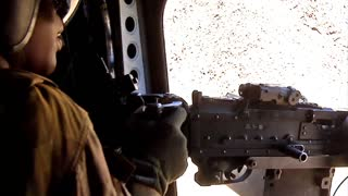 Chinook door gunner fires his machine gun