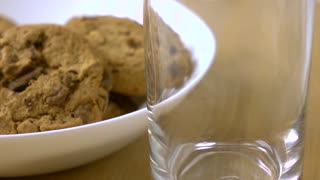 Chocolate chip cookies and milk being poured in a glass. 4K close-up super slow motion shot