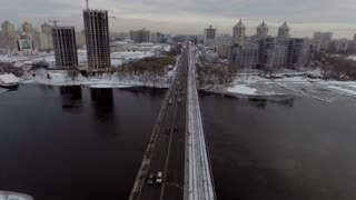 City Traffic on the bridge, it's snowing. Shooting from the air, 4k video