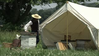 civil war era beekeeper working around tent in open field