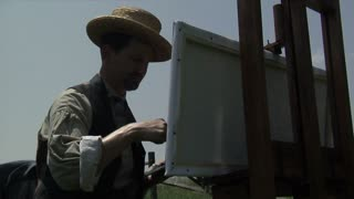 civil war era painter in straw hat working outdoors