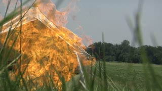 civil war era tent on fire in tall grass