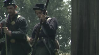 civil war era union soldiers reload and fire muskets by barn