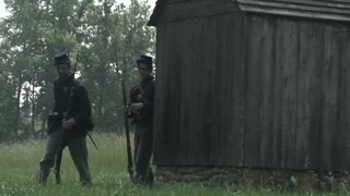 civil war era union soldiers walking away from barn post, wide shot