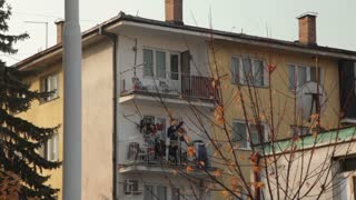 Civilian Hanging Laundry on Balcony of Apartment