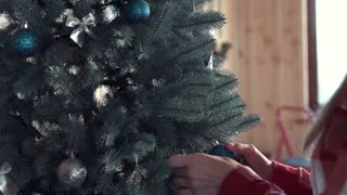 Close 4K shot of pretty young blond woman decorting Christmas tree at home with silver and blue balls