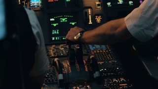 Close shot of cabin interior of Airbus A319 A320 A321. Flight deck and pedestal. Thrust and thrust reverse control levers with co-pilot's hand in white shirt