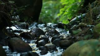 Close shot of dark rocks with water running