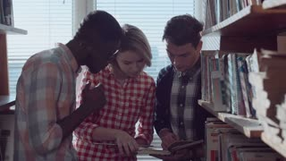 Close shot of three different ethnic people sitting on a window and discussing the books in the library between stacks