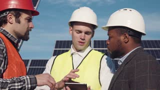 Close shot of three men standing in solar power station and discussing something