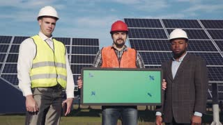 Close shot of trio of solar panel engineers with green screen panel and executive surrounded by large collector arrays outside