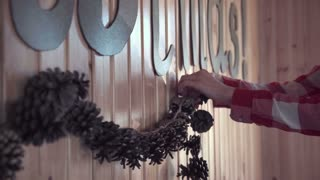 Close shot of woman hands decorating a wooden wall with Merry Christmas sign at home with garland from cones