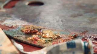Close up details of yellow oil paint on an artists pallet in large blobs around the edge in a variety of colors and blends, with copy space
