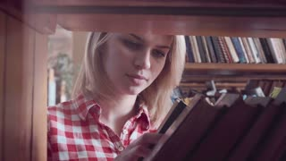 Close up intimate shot of pretty young girl student with blonde hair looking through books standing behind bookshelf in library towards slowly moving camera