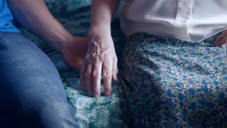 Close-up of a young man taking a hand of an elderly woman. Grandson caring a grandmother. An old family member at home.