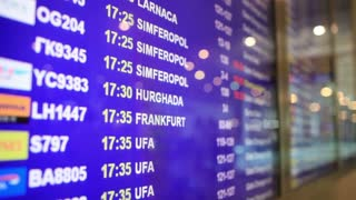 Close-up of arrival and departure board in airport. Flight information on blue field with language changing from English to Russian.
