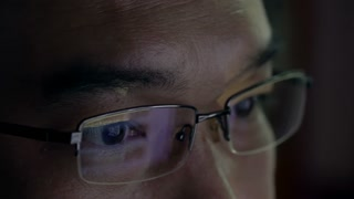 Close-up of asian man with social media reflecting in his glass lenses