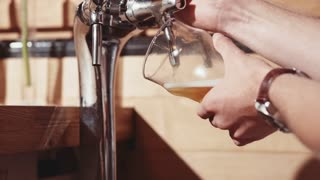 Close-up of bartender's hands pouring a pint of beer or lager. Slow Motion 240 fps. Barman is working at the bar.