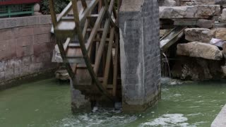 Close Up of Chinese Water Wheel Churning Water Below