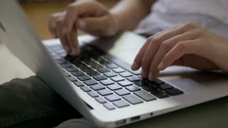 Close-up of female hands typing on the laptop keyboard.