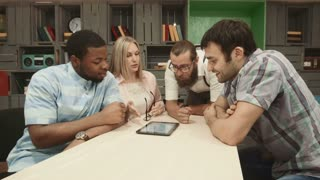 Close-up of four adults using tablet at table in coworking room