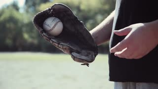 Close Up of Man Wearing Baseball Glove and Tossing Baseball from Hand to Hand During Baseball Game Outdoors in Field on Sunny Day in Summer 4K